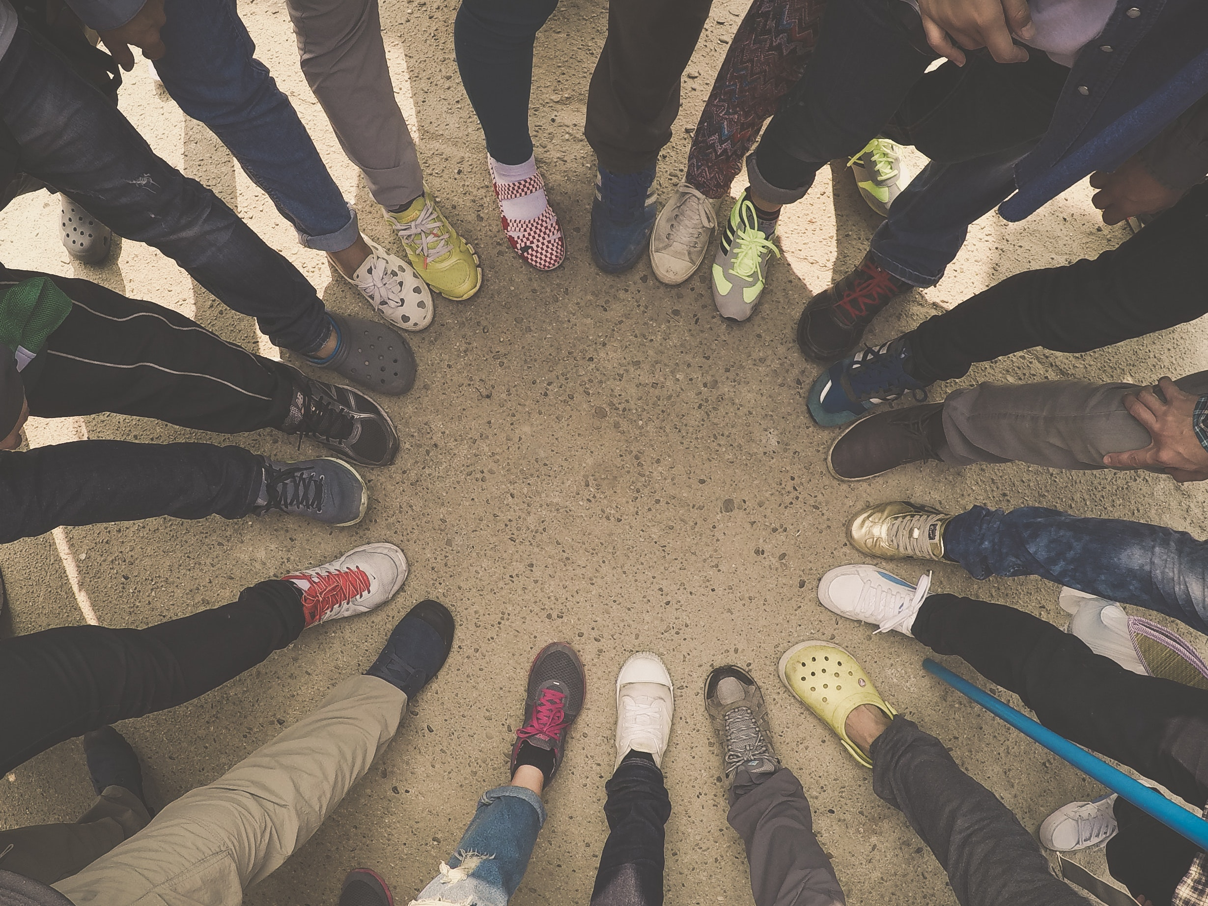 a group of people stand in a circle, lining up their feet