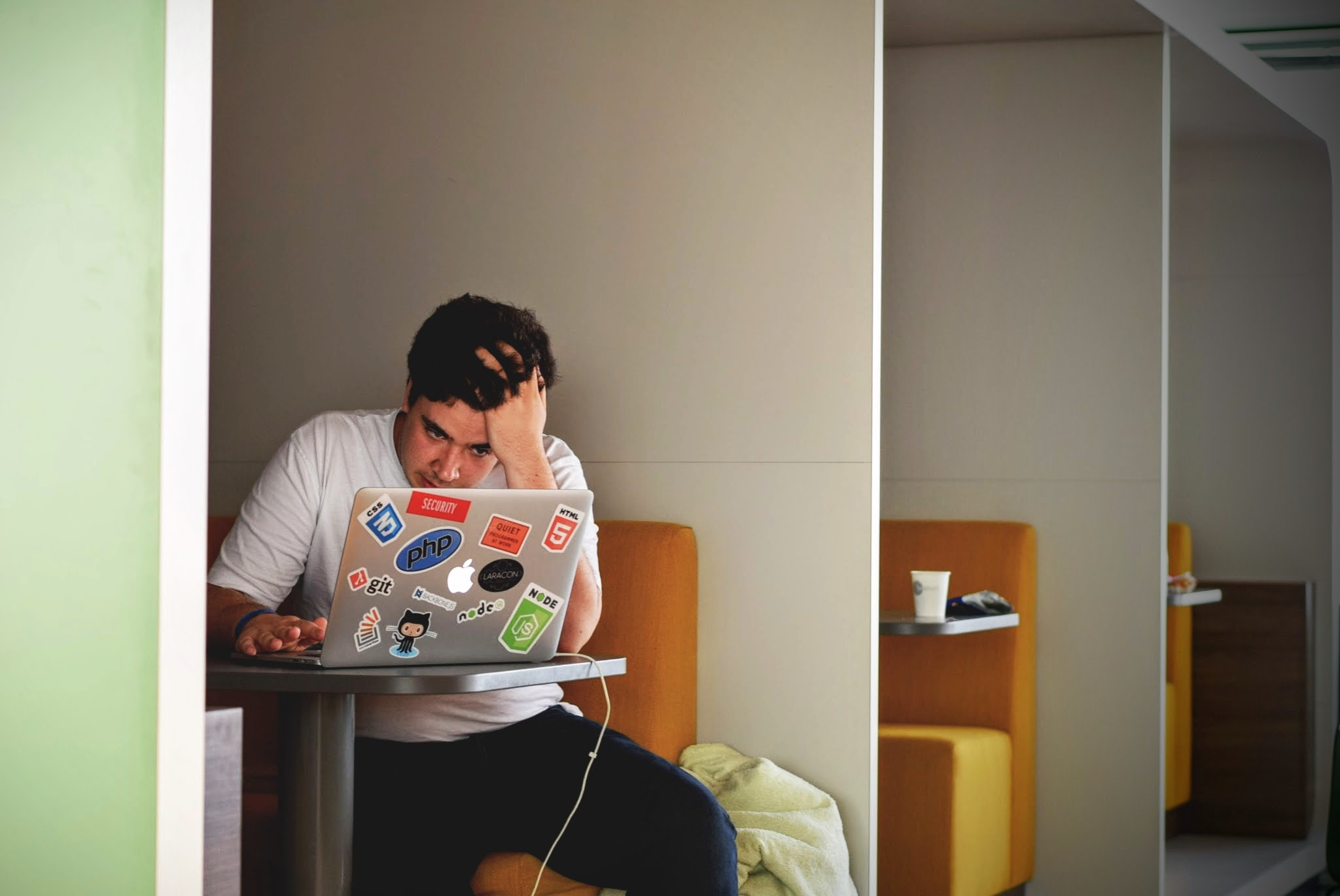 a student works on his laptop, looking stressed