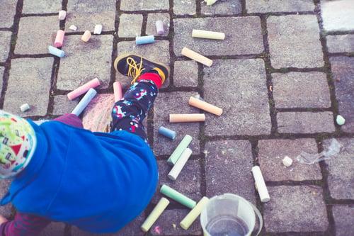 a child plays with sidewalk chalk