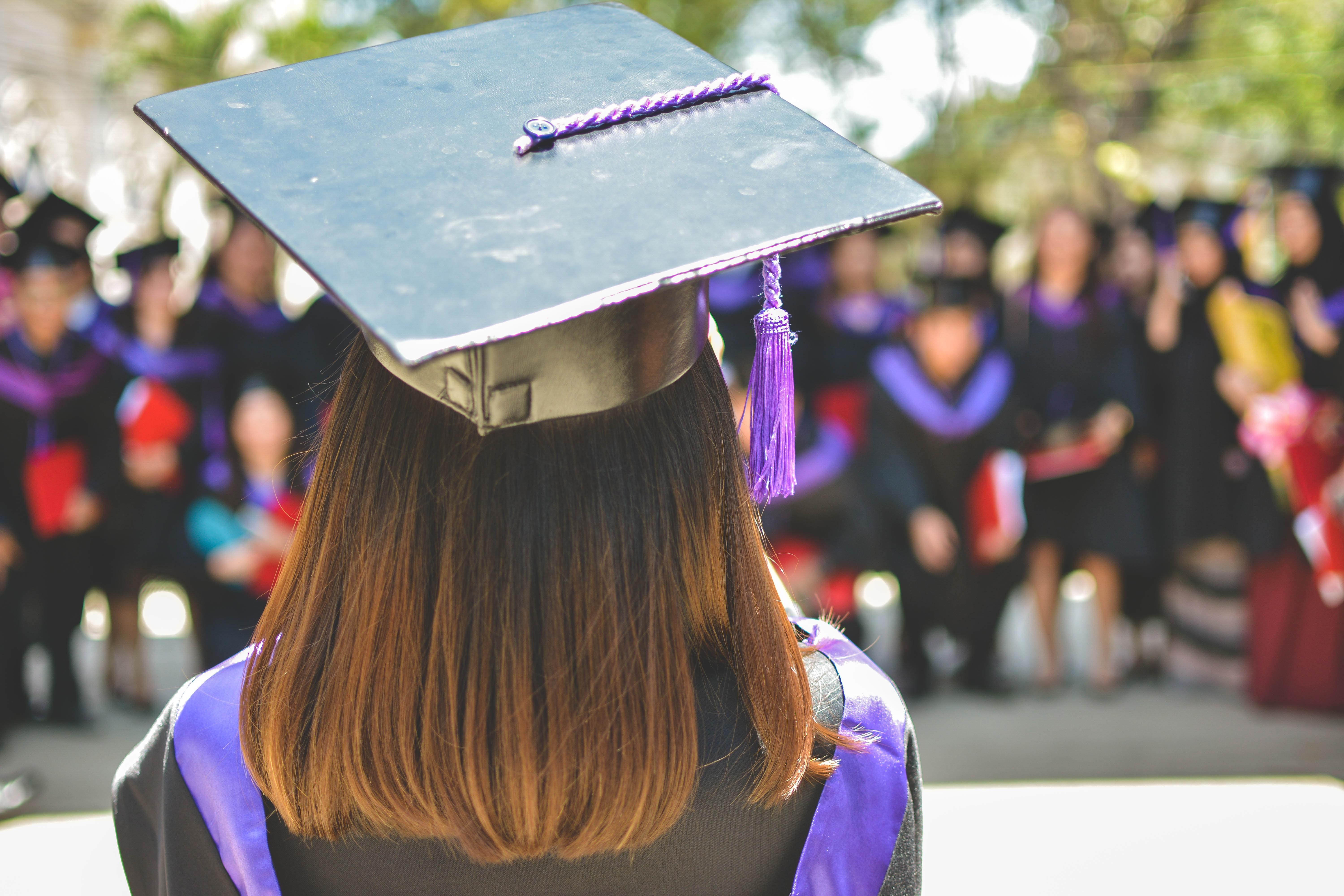a student is shown wearing a graduation gown and cap