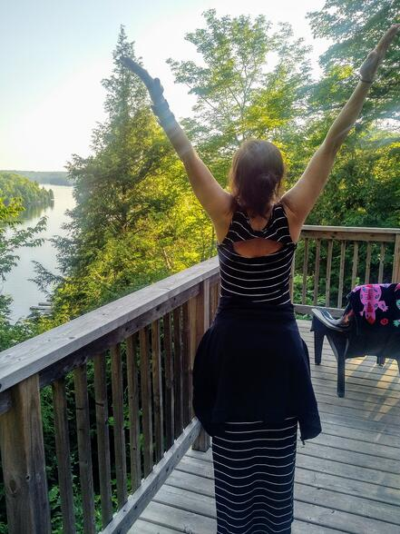 Dr. Diana Petrarca, with her arms open over her head, in celebration of being in the outdoors.