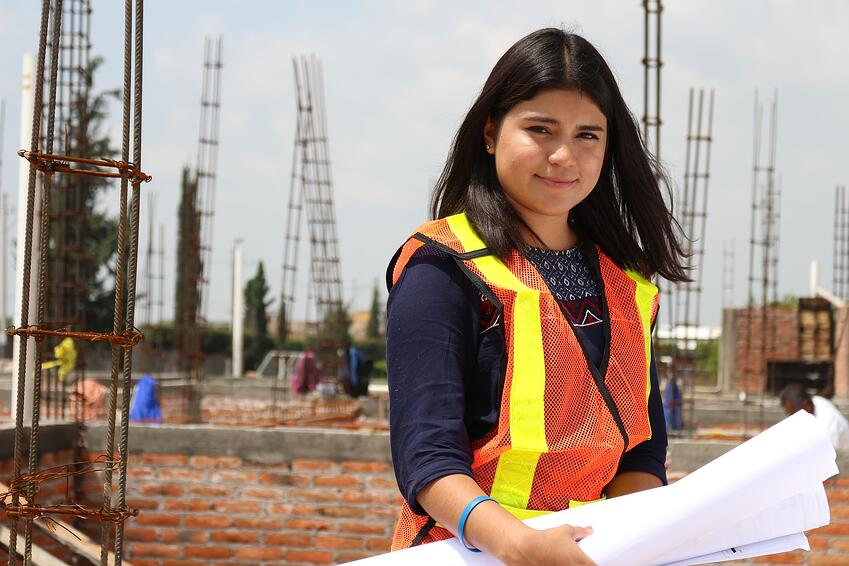 a woman poses on a job site
