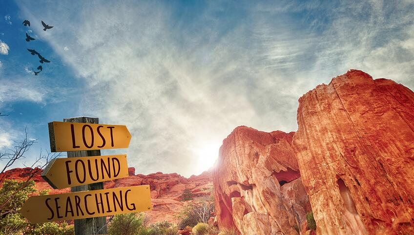 a sign that says lost, found, searching in a valley of red rocks