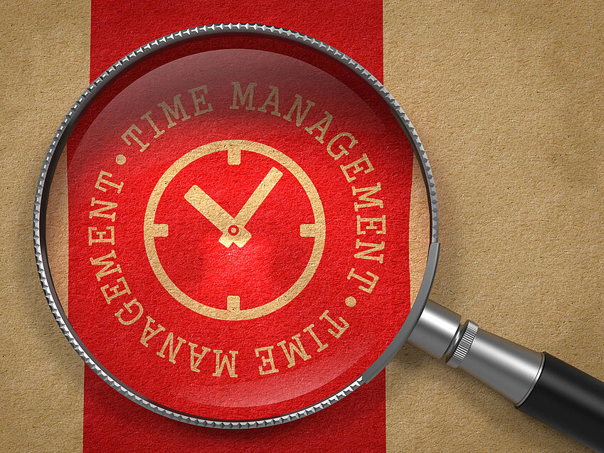Magnifying glass over a time management graphic