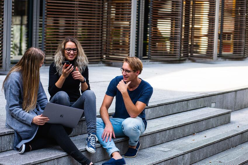 3 students sitting on steps