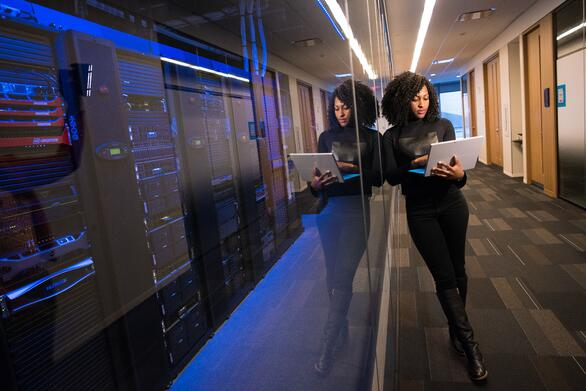 woman-holding-laptop-beside-glass-wall-1181316